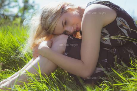 Pretty blonde in sundress sitting on grassの素材 [FYI00002567]