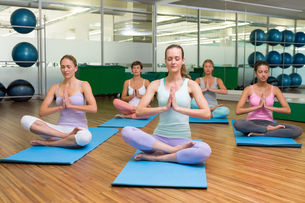 Smiling yoga class in lotus pose in fitness studioの素材 [FYI00002570]