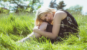 Pretty blonde in sundress sitting on grassの写真素材 [FYI00002571]