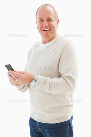 Happy mature man sending a textの写真素材 [FYI00002576]