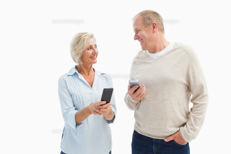 Happy mature couple using their smartphonesの写真素材 [FYI00002581]