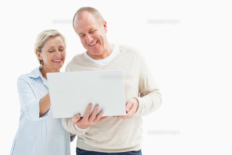 Happy mature couple using laptopの写真素材 [FYI00002585]