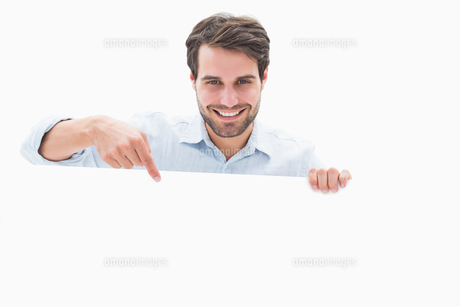 Attractive young man smiling and holding posterの写真素材 [FYI00002588]