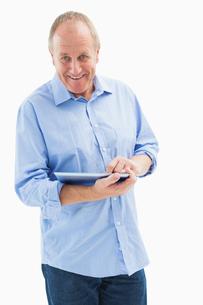 Happy mature man using his tablet pcの写真素材 [FYI00002589]