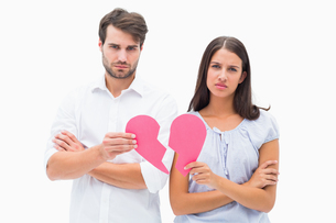 Upset couple holding two halves of broken heartの素材 [FYI00002603]