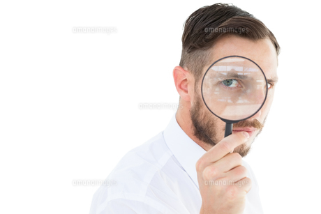 Geeky businessman looking through magnifying glassの素材 [FYI00002624]
