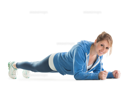 Smiling young woman in basic plank postureの写真素材 [FYI00002627]