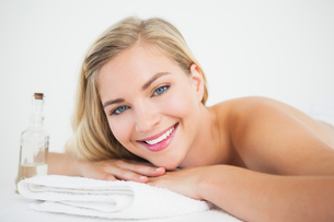 Beautiful blonde lying on massage table smiling at cameraの写真素材 [FYI00002649]