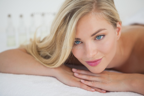 Beautiful blonde lying on massage table smilingの写真素材 [FYI00002652]