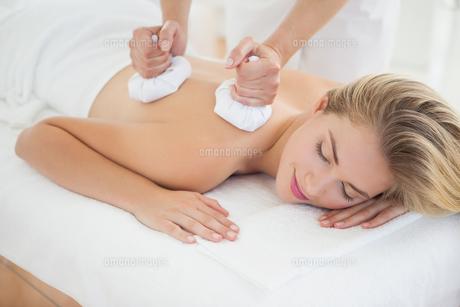 Beautiful blonde enjoying a herbal compress massageの写真素材 [FYI00002653]