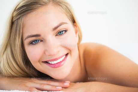 Beautiful blonde lying on massage table smiling at cameraの写真素材 [FYI00002655]