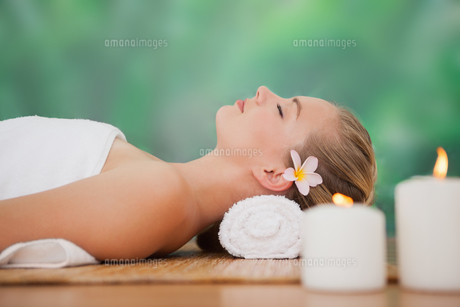 Peaceful blonde lying on bamboo mat with candlesの写真素材 [FYI00002674]