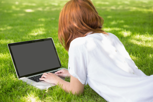 Redhead using laptop in the parkの写真素材 [FYI00002684]
