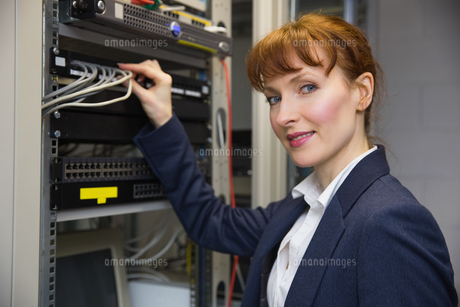 Pretty computer technician smiling at camera while fixing serverの写真素材 [FYI00002691]