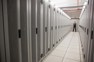 Serious technician standing in server hallwayの写真素材 [FYI00002692]
