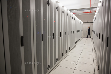 Technician walking in server hallwayの写真素材 [FYI00002693]