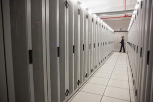 Technician walking in server hallwayの写真素材 [FYI00002693]