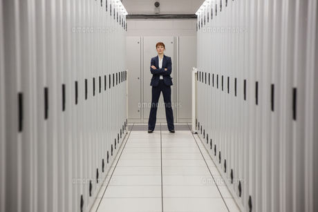 Serious technician standing in server hallwayの写真素材 [FYI00002694]