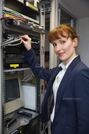 Pretty computer technician smiling at camera while fixing serverの写真素材 [FYI00002695]