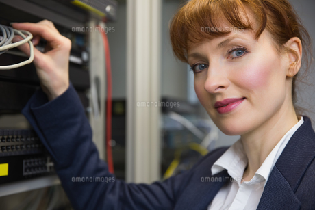 Pretty computer technician smiling at camera while fixing serverの写真素材 [FYI00002696]