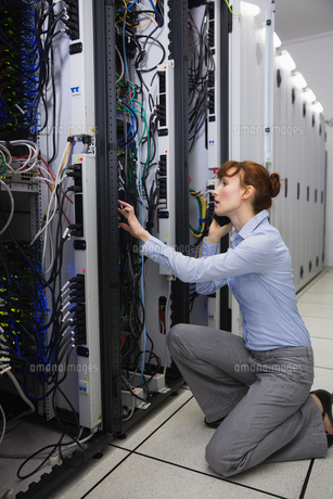 Serious technician talking on phone while analysing serverの写真素材 [FYI00002697]