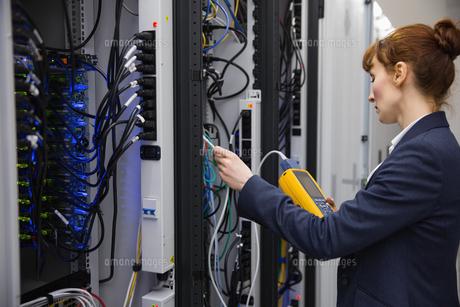 Technician using digital cable analyzer on serverの写真素材 [FYI00002699]