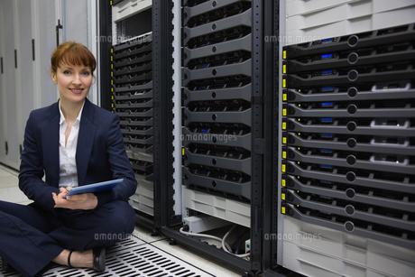 Technician sitting on floor beside server tower using tablet pcの写真素材 [FYI00002700]