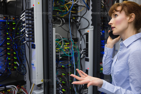 Technician talking on phone while analysing serverの写真素材 [FYI00002701]