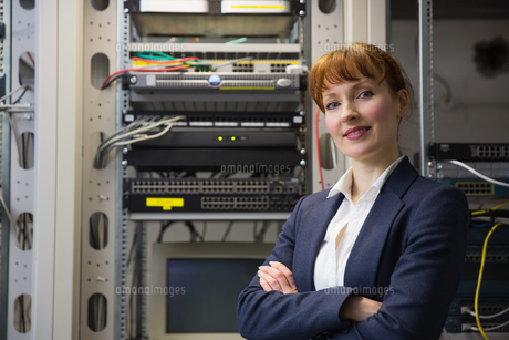 Pretty computer technician smiling at camera while fixing serverの写真素材 [FYI00002702]
