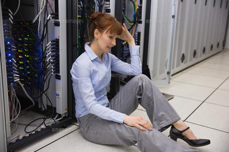 Stressed technician sitting on floor beside open serverの写真素材 [FYI00002703]