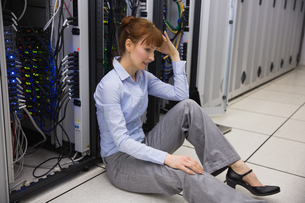 Stressed technician sitting on floor beside open serverの写真素材 [FYI00002703]