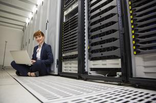 Technician sitting on floor beside server tower using laptopの写真素材 [FYI00002704]
