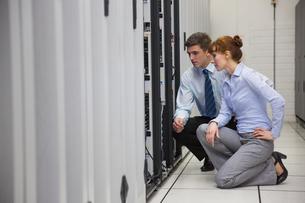 Team of technicians kneeling and looking at serversの写真素材 [FYI00002709]