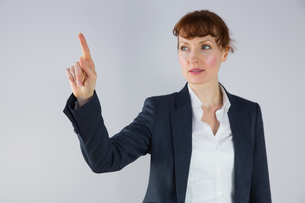 Businesswoman in suit pointing fingerの写真素材 [FYI00002712]