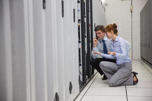 Team of technicians kneeling and looking at serversの写真素材 [FYI00002713]