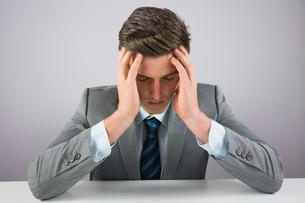 Stressed businessman sitting at deskの素材 [FYI00002714]