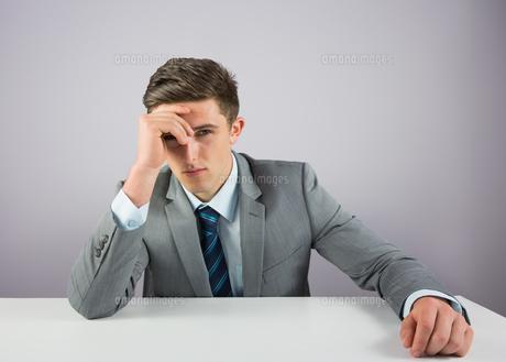 Serious businessman sitting at deskの素材 [FYI00002717]