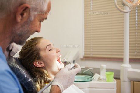 Dentist examining a patients teeth in the dentists chair under bright lightの素材 [FYI00002733]