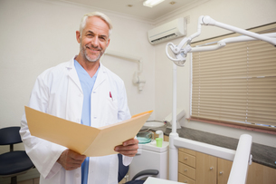 Dentist smiling at camera holding folderの写真素材 [FYI00002737]