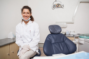 Dentist smiling at camera beside chairの写真素材 [FYI00002740]