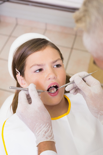 Pediatric dentist examining a patients teeth in the dentists chairの写真素材 [FYI00002741]
