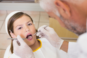 Pediatric dentist examining a patients teeth in the dentists chairの写真素材 [FYI00002743]