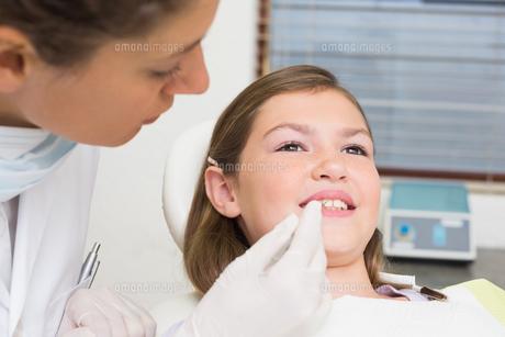 Pediatric dentist examining little girls teeth in the dentists chairの写真素材 [FYI00002744]