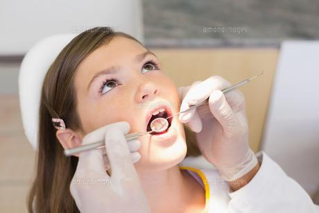 Pediatric dentist examining a little girls teeth in the dentists chairの素材 [FYI00002748]