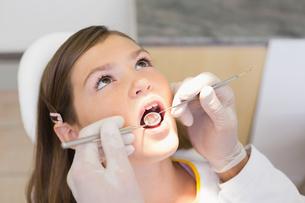 Pediatric dentist examining a little girls teeth in the dentists chairの写真素材 [FYI00002748]
