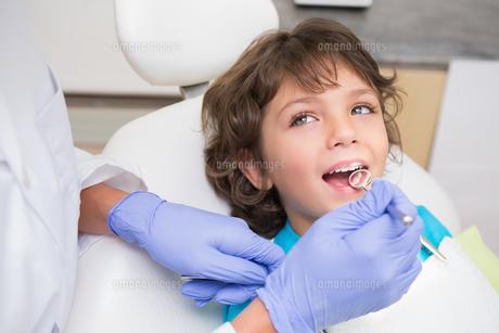 Pediatric dentist examining a little boys teeth in the dentists chairの写真素材 [FYI00002754]