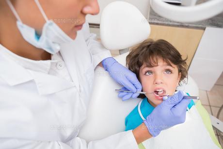 Pediatric dentist examining a little boys teeth in the dentists chairの写真素材 [FYI00002755]