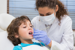 Pediatric dentist examining a little boys teeth in the dentists chairの写真素材 [FYI00002761]