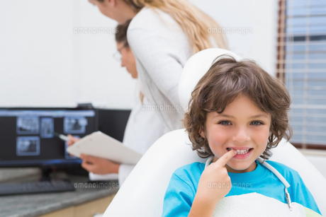 Little boy smiling at camera with mother and dentist in backgroundの素材 [FYI00002768]