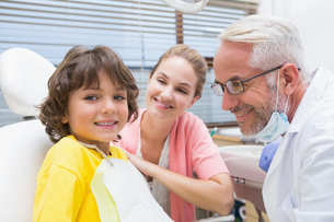 Little boy smiling at camera with mother and dentist beside himの写真素材 [FYI00002771]